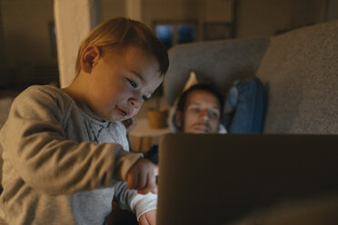 Litle girl with parents looking at laptop on the couch in the dark - KNSF03413