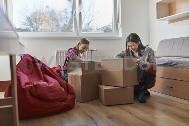 Two young women unpacking cardboard boxes in a room - ZEDF01079