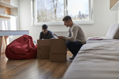 Two young men unpacking cardboard boxes in a room - ZEDF01082