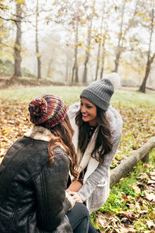 Two pretty women relaxing in an autumnal forest - MGOF03696