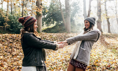 Two pretty women having fun in an autumnal forest - MGOF03699