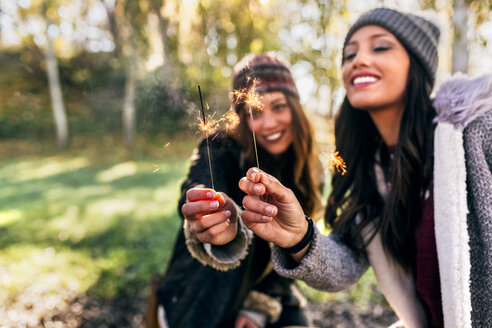 Two happy women holding sparklers in an autumnal forest - MGOF03702