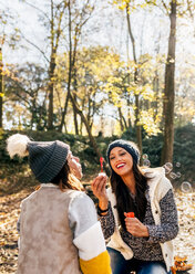 Two pretty women having fun with soap bubbles in an autumnal forest - MGOF03705