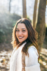 Portrait of a beautiful smiling woman in an autumnal forest - MGOF03708