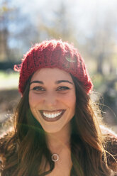 Portrait of a beautiful smiling woman wearing wooly hat - MGOF03711