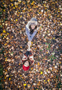 Two happy women standing in autumn leaves holding hands - MGOF03720