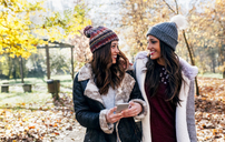 Two pretty women with cell phone smiling at each other in an autumnal forest - MGOF03726