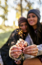 Hands of two women holding sparklers outdoors - MGOF03729