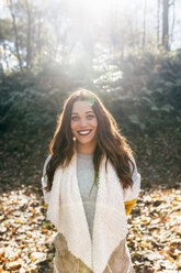 Portrait of a beautiful smiling woman in an autumnal forest - MGOF03732