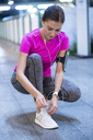 Young woman in pink sportshirt listening to music and tying her sneakers - SBOF00980