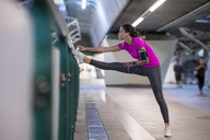 Young woman in pink sportshirt listening to music and stretching in urban metro station - SBOF00983