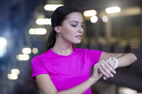 Young woman in pink sportshirt checking her smartwatch - SBOF00986