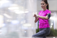 Young woman in pink sportshirt listening to music and checking her smartwatch in modern urban setting - SBOF00992