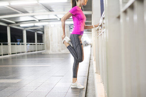 Young woman in pink sportshirt stretching in modern metro station at night - SBOF00998