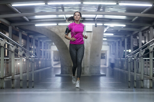 Young woman in pink sportshirt running in modern metro station at night - SBOF01001