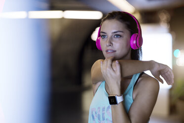 Young woman with pink headphones stretching and listening to music in modern urban setting at night - SBOF01007