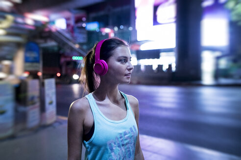 Young woman in pink sportshirt in modern urban setting at night - SBOF01010