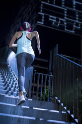 Young woman with pink headphones running upstairs in modern urban setting at night - SBOF01013