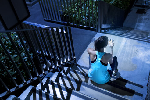 Young woman sitting on stairs and checking her smartphone in modern urban setting at night - SBOF01016