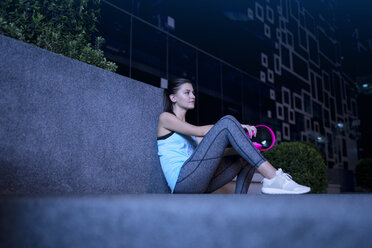 Young woman with pink headphones sitting on the ground in modern urban setting at night - SBOF01019