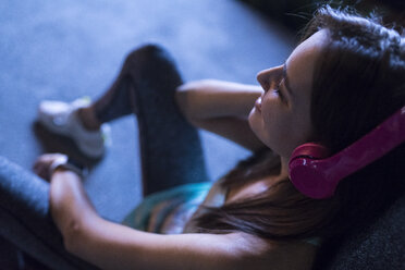 Happy young woman with pink headphones listening to music in modern urban setting at night - SBOF01022