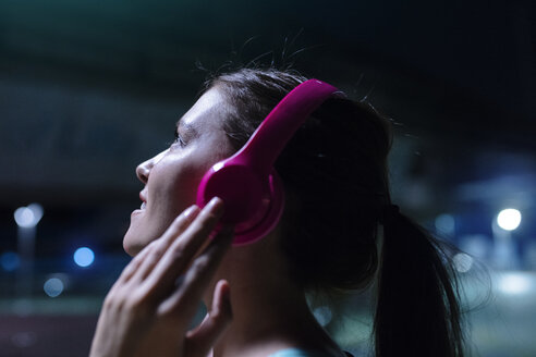 Happy young woman with pink headphones listening to music in modern urban setting at night - SBOF01025