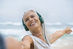 Portrait of beautiful smiling senior woman dancing on beach - SBOF01030