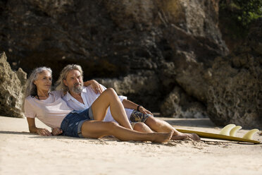 Handsome senior couple with surfboard lying on beach - SBOF01033