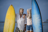 Affectionate senior couple with surfboards at beach - SBOF01036