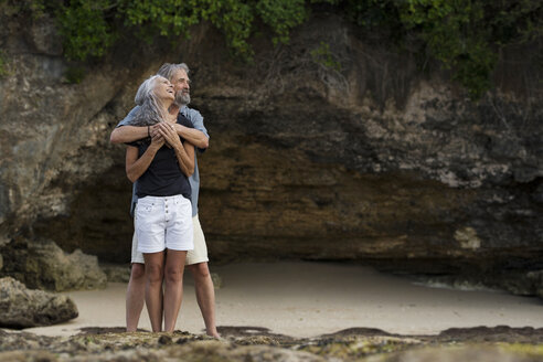 Affectionate senior couple hugging at beach - SBOF01042