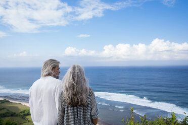 Senior couple looking at the ocean, rear view - SBOF01057