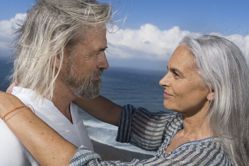 Affectionate senior couple looking into each others eyes in front of the sea - SBOF01063