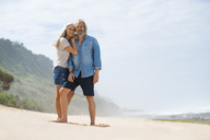 Affectionate senior couple standing on the beach - SBOF01069