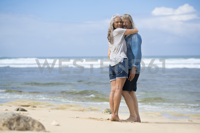 Affectionate senior couple standing on the beach - SBOF01075