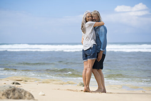 Affectionate senior couple standing on the beach - SBOF01075