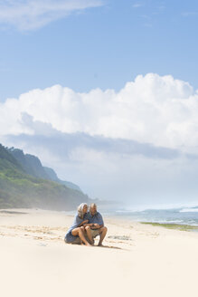 Senior couple sitting on the beach, wrapped in a blanket - SBOF01084