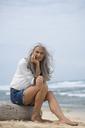 Beautiful senior woman sitting at the beach - SBOF01087