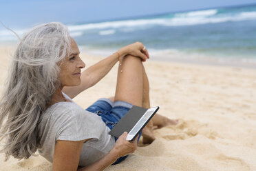 Beautiful smiling senior woman lying at the beach, holding e-book - SBOF01090