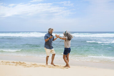Handsome senior couple with headphones dancing on the beach - SBOF01093