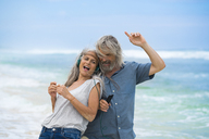 Handsome senior couple with headphones dancing on the beach - SBOF01096