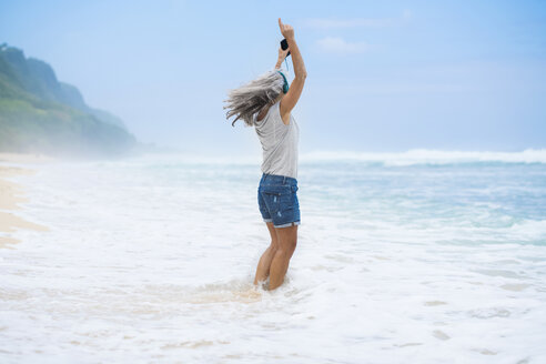 Senior woman with headphones dancing on the beach - SBOF01099