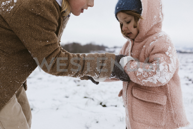 Brother and little sister together on snow-covered meadow - KMKF00125