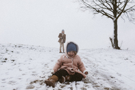 Crying girl on snow-covered meadow with brother in background - KMKF00128