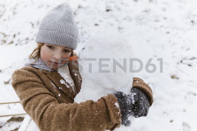 Boy hugging a snowman - KMKF00131