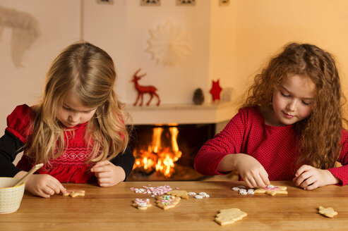 Little girls garnishing Christmas cookies with hundreds and thousands - NEKF00005