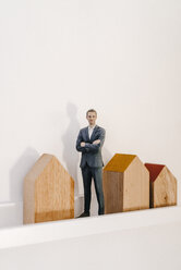 Businessman figurine standing by wooden house models - FLAF00001