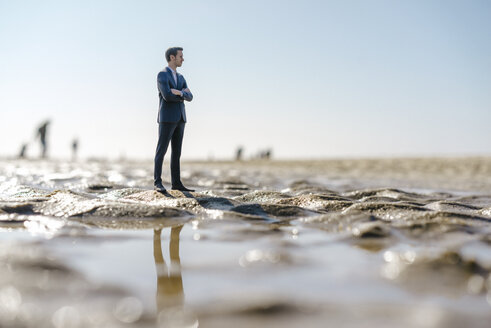 Businessman figurine standing on wet beach, looking at distance - FLAF00004