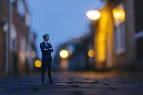 Businessman figurine standing in street in front of houses - FLAF00007