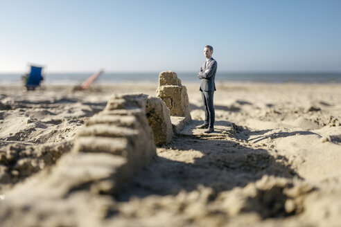 Businessman figurine standing on sand by sand buildings - FLAF00010