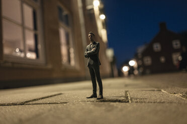 Businessman figurine standing in street in front of houses - FLAF00013